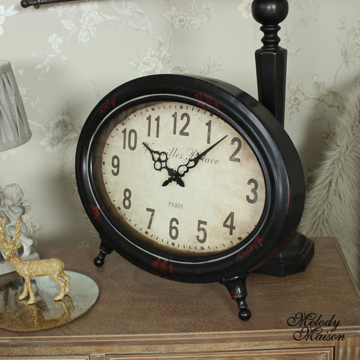 """Vintage Oval Mantel Clock A fantastic looking vintage style mantel clock With an aged effect cream clock face with the words, """"Versailles Palace Paris"""", printed on the front and elegant hands The frame is made from metal and painted in an aged, rustic brown finish Freestanding with metal pull out stand on the back, takes x1 AA battery"""