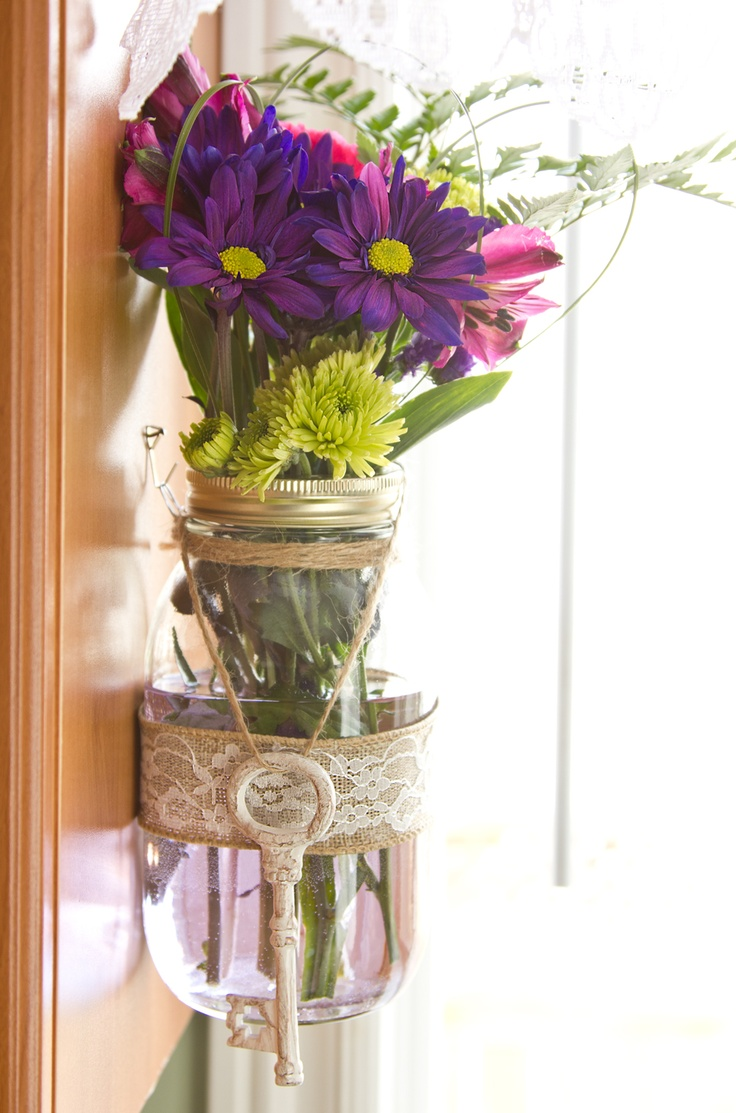 Large mason jar hanging above sink. Materials used: large mason jar, wire, twine, burlap ribbon, lace, vintage key, fresh flowers