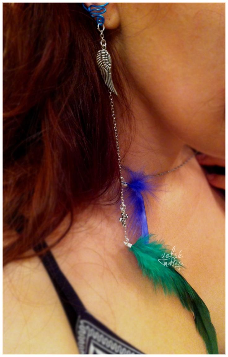cuff realizado en alambre de aluminio azul con plumas de marabú azul y cuello de gallo verde, cadena plateada con adornos de ala y cruz bañados en plata