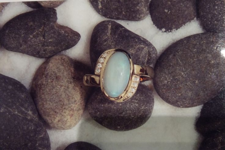 Blue toned milk opal rim set with a spiral of pave set  diamonds and cross over band