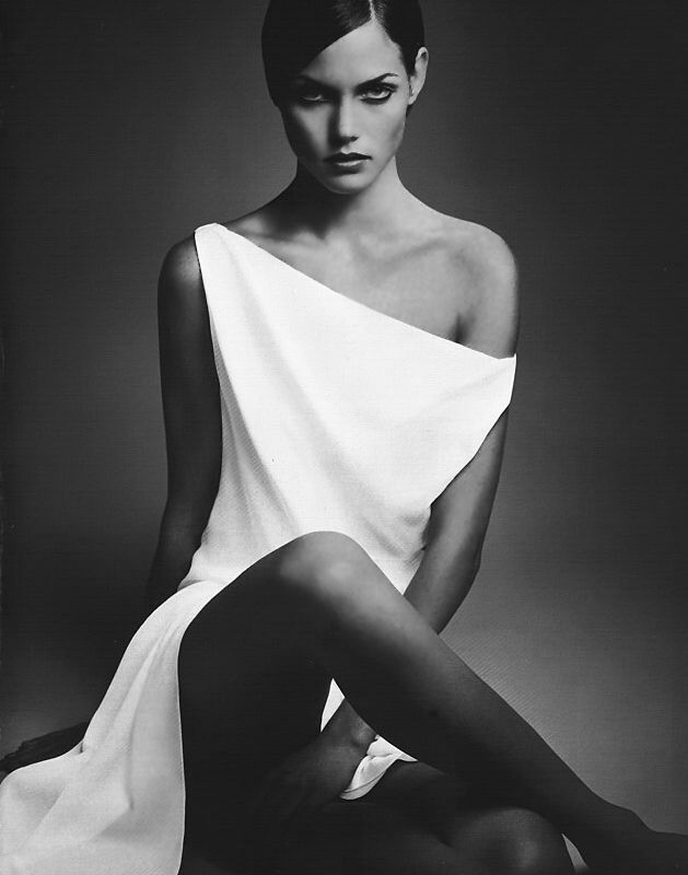 Black and white studio modeling shot. Stark white dress stands out against dark shadowing.