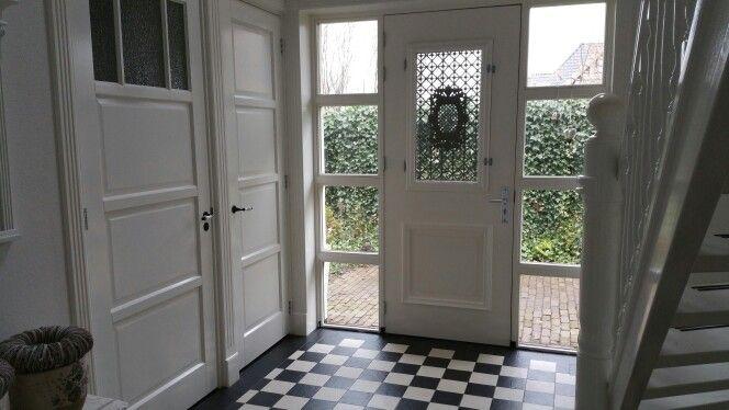 De klassieke voordeur met gietijzeren raamrooster past perfect in het…