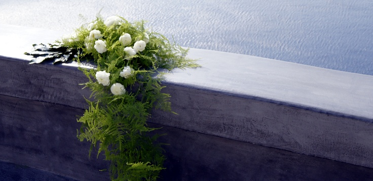 Andronis II - Registrar table centerpiece with Avalance roses, white Ranunculus, Plumosus and Fatsia Japonica.  See also the bridal bouquet.    Wedding venue: Andronis Boutique Hotel, Oia  Wedding planner: Sunrise Travel Consultants Hong Kong