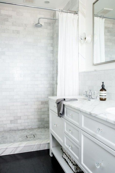 Walk in shower in a NYC bathroom with marble tile and marble counters, white cabinets, designed by Katie Martinez.