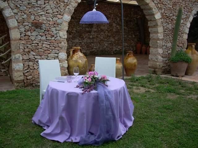 Tavolo rotondo in giardino, con composizione floreale a lato