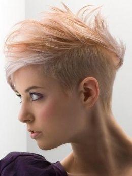 Les cheveux de cette jeune femme ont été rasés sur les côtés et à l'arrière, pour ne laisser qu'un épais mohawk sur le dessus de sa tête, qui a été coiffé vers l'avant. Le coiffeur a joliment réalisé des mèches gris argenté et roux pâle pour un effet vraiment craquant.