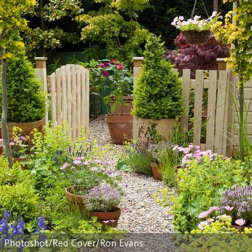 Cremefarbenes Gartentor aus Holz und Kiesweg im farbenfrohen Garten. …