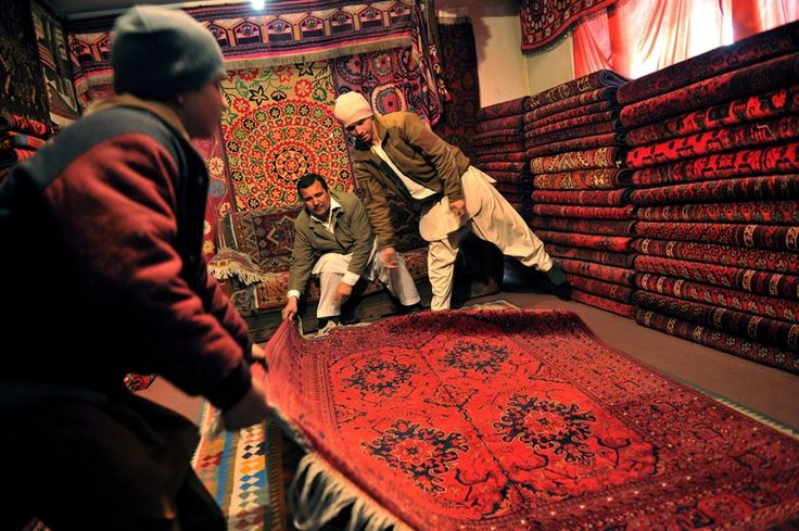 Afghan shopkeeper Ismail Temorzada, 45, center, displays a carpet to customers in his shop on Chicken Street in Kabul, March 3.