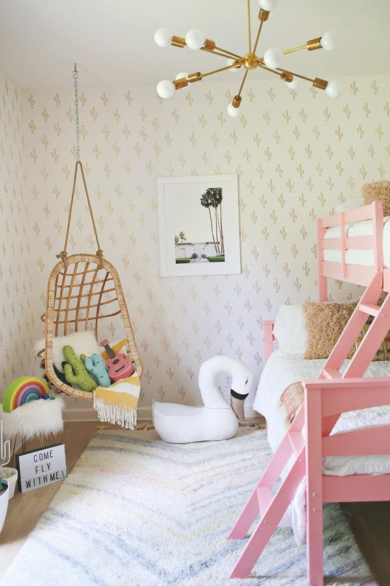 Southwestern chic bunk room features a fun hanging chair, tiered bunks and super fun cactus wall detail (it was a diy project!). Spotted also on A Beautiful Mess.