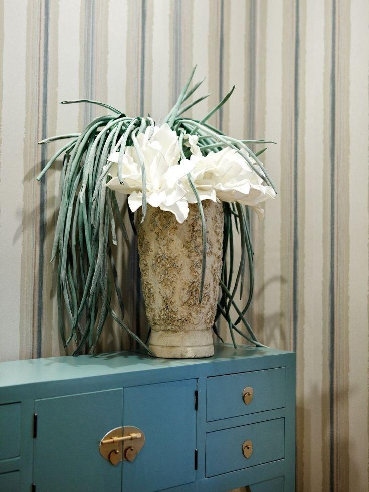 Flores artificiales en el jarrón de la consola, todo un acierto .. ah y el papel de rayas aporta altitud.