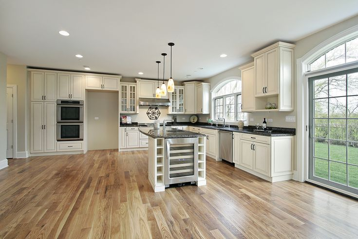 Expansive kitchen featuring white throughout, plus light hardwood flooring and island with built-in wine cooler.