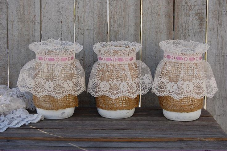 3 shabby chic mason jars hand painted in soft white, lightly distressed and wrapped with burlap, white lace with pink ribbon and a protective coating. They are not painted on the inside and can hold w