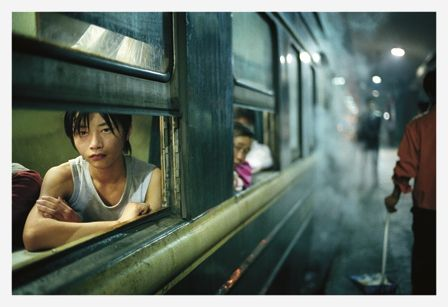 A young man sitting by one of the few windows that aren't broken, Guangdong Province//Andreas Seibert - From Somewhere to Nowhere - China's Internal Migrants