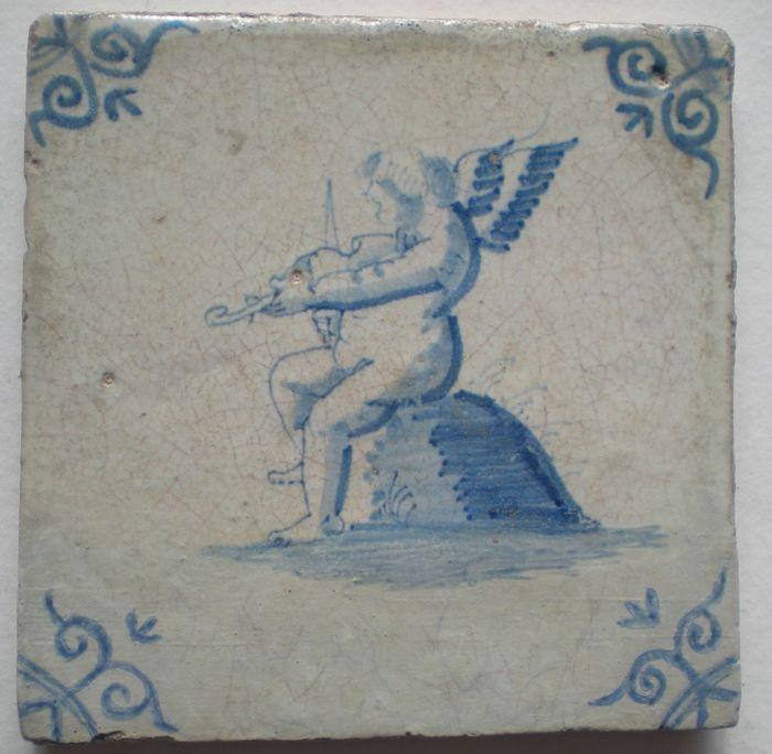 Antieke tegel met Cupido met viool  Zeldzaam !  Hoekmotief ossekop Conditie oude restauraties  Maat ca 13x13x1, cm  GEEN RESTAURATIES IN DE VOORSTELLING