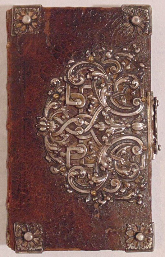 """Ca. 1777. 6.5"""" x 4"""". With decorative manuscript prize leaf inserted at front and dated 1777. Leather over wooden boards with silver corners and large, elaborate floral clasps (front and rear). Rubbing to extremities, all intact. Gilt edges rubbed, and general patina to clasps and corners. Contains """"Vollstandiges Gesangbuch aus den besten Liedersammlungen,"""" Lindau, 1769."""