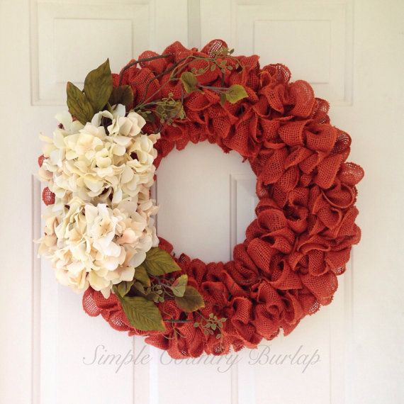 Primitive fall or autumn burlap wreath. Ruffle burnt orange burlap wreath with greenery and cream hydrangeas. Please contact me for other colors. This is a great wedding, housewarming, birthday, or any got idea!! Measure approximately 22 side to side. Please contact me if you are interested in larger sizes or other decorations! ***Each wreath is handmade and may differ slightly from the picture. I strive to make each wreath full and even