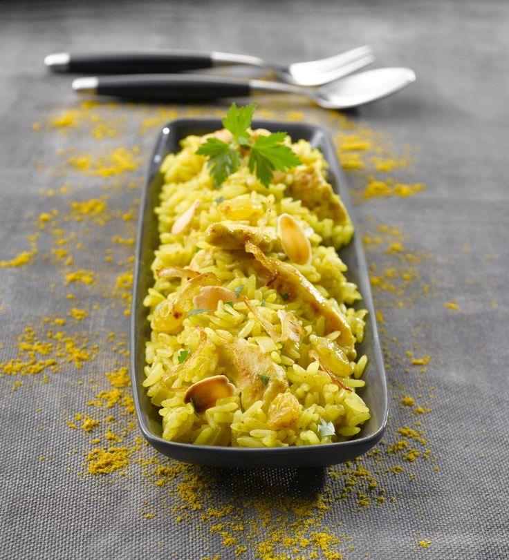 Hachez les oignons. Emincez le poulet. Dans une cocotte, faites dorer le poulet avec l'huile, ajoutez les oignons et poursuivez la cuisson 3 minutes. Ajoutez le riz. Mélangez. Ajoutez 800 ml d'eau et les bâtonnets de bouillon, le curry et les raisins. Laissez cuire 14 minutes. Parsemez d'amandes effilées grillées et de persil ciselé avant de servir.