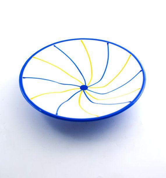 Het unieke ontwerp van deze kleurrijke gesmolten glazen kom zal iedereen vragen waar op aarde vond u het hebben. Vrolijk geel en kobalt blauw glas stringers spiraal naar buiten vanuit het midden van deze decoratieve schotel, het creëren van een aantrekkelijke patroon op het wit glas basis. De achterzijde van de kom is een prachtige kobalt blauw. Of u het als een vrucht of pasta kom, of een cool stukje gebruikt toe te voegen aan uw huis decor, is dit een gerecht dat je elders niet vindt. Wil…