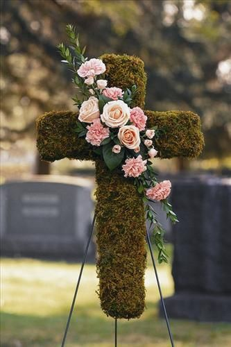 Moss Cross  - accented with a diagonal swag of pink and peach flowers (roses and  carnations)