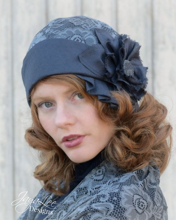 This Art Deco Style cloche hat has a deep crown made of slate blue/gray linen fabric, that is overlaid with gray blue lace. The brim folds up