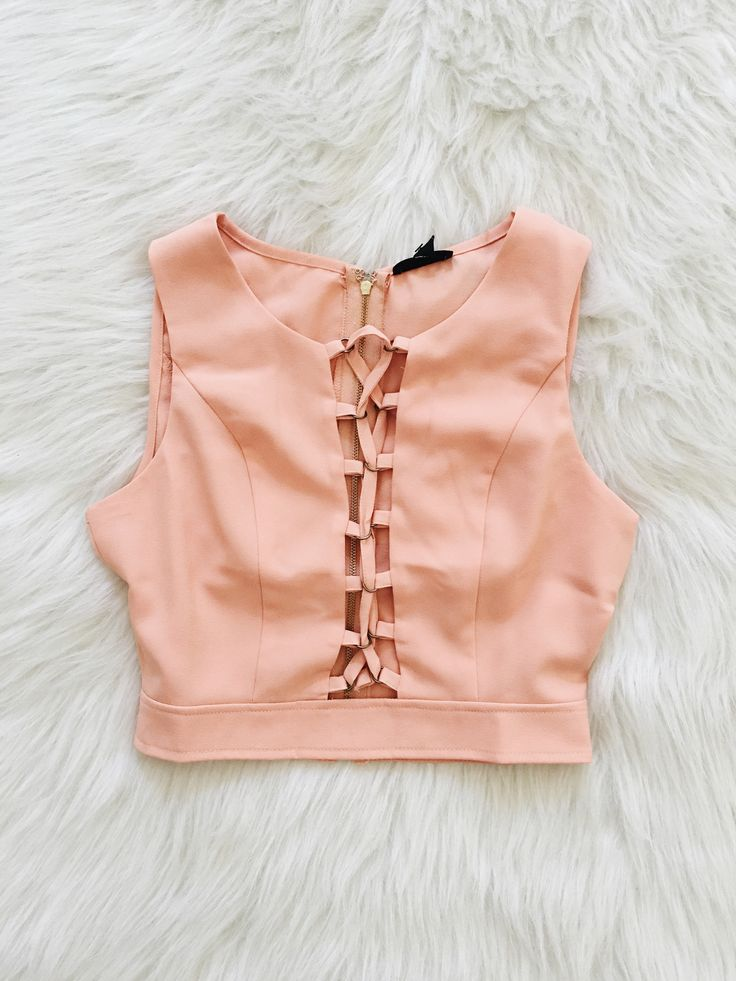 This sleeveless crop top features a laceup detail on center front, a round neckline and a fitted silhouette.