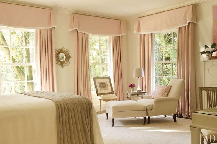 A guest room includes a chair and ottoman from Kasler's Hickory Chair collection and a carpet she designed for Safavieh; the window treatments are made of a Nancy Corzine linen.