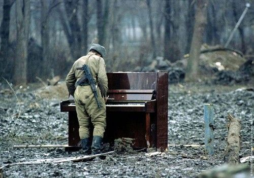 A Russian soldier plays an abandoned piano.