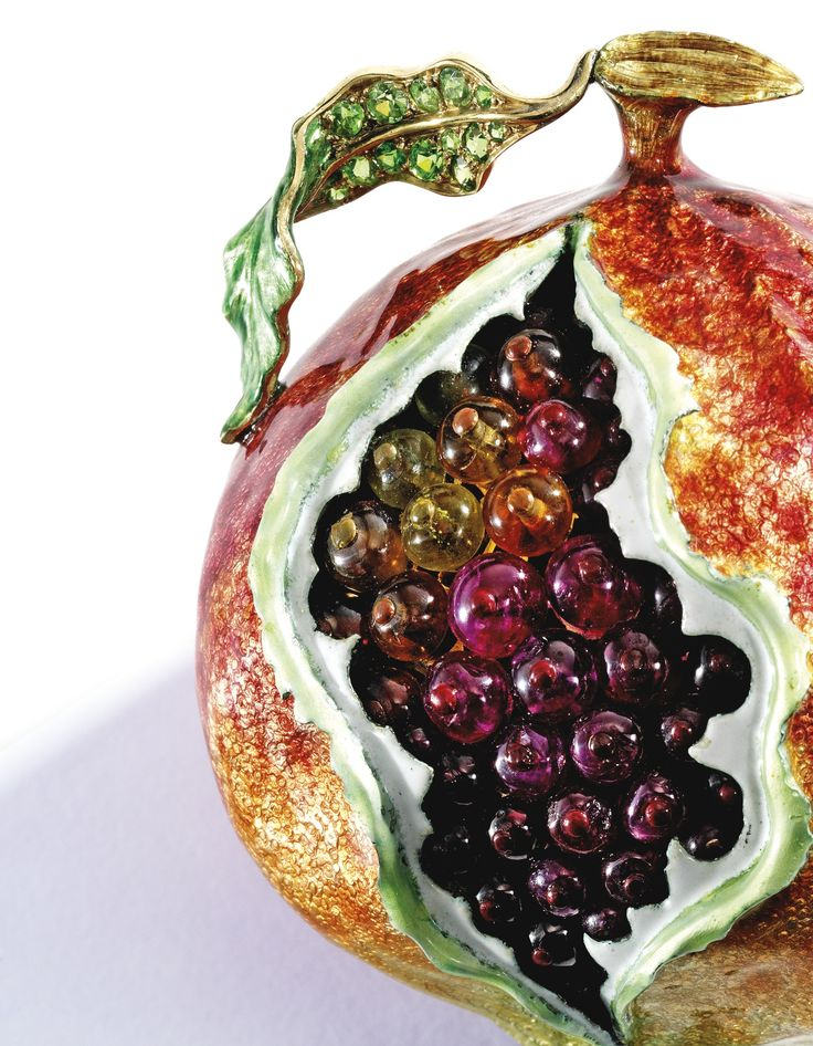 PROPERTY FROM THE COLLECTION OF MRS PAUL 'BUNNY' MELLON: A Gold, Gem-Set and Enamel Table Ornament, Verdura, the fanciful pomegranate highlighted in vibrant multi-colored enamel, with numerous ruby, pink tourmaline and citrine 'seeds,' the stem and leaves set with round demantoid garnets and colored diamonds ~ .35 carat.