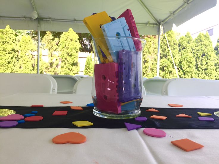 """90's theme party centerpiece. Ordered the vases {Amazon} 2 packs of 4 - 6"""" cylinder vases. Cassettes {Amazon} - they sell them in different colors - I ordered them in white 100 pack - spray painted them myself. Colorful confetti {Jo-Ann's} which isn't necessarily confetti I just used it that way. There are those styrofoam shapes in the kids arts and crafts section."""