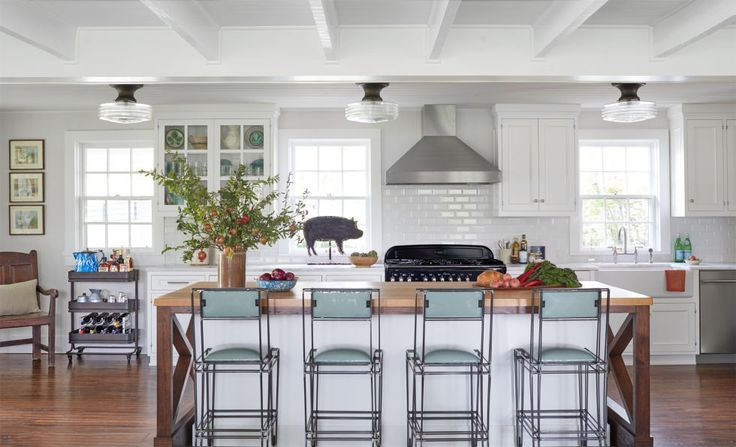 Modern Country:  In the kitchen of this Tennessee home, traditional country features—blue splatterware, white ceramic walls, an apron-front sink—are offset by pale blue iron barstools from Mexico and an industrial bar cart. The metal pig (and former weather vane) adds all kinds of character on its own.