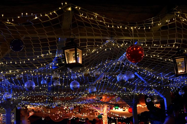 Ceiling decorated with fishing net, fairy lights, lanterns and disco balls