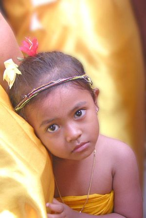 A Balinese Child clings to her mother's bosom during a ceremony.