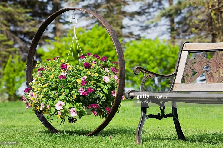 A hanging basket with Petunias, Verbena and Million Bells next to a garden bench. The basket is hanging on an antique steel wagon wheel that has been recycled into a plant holder.