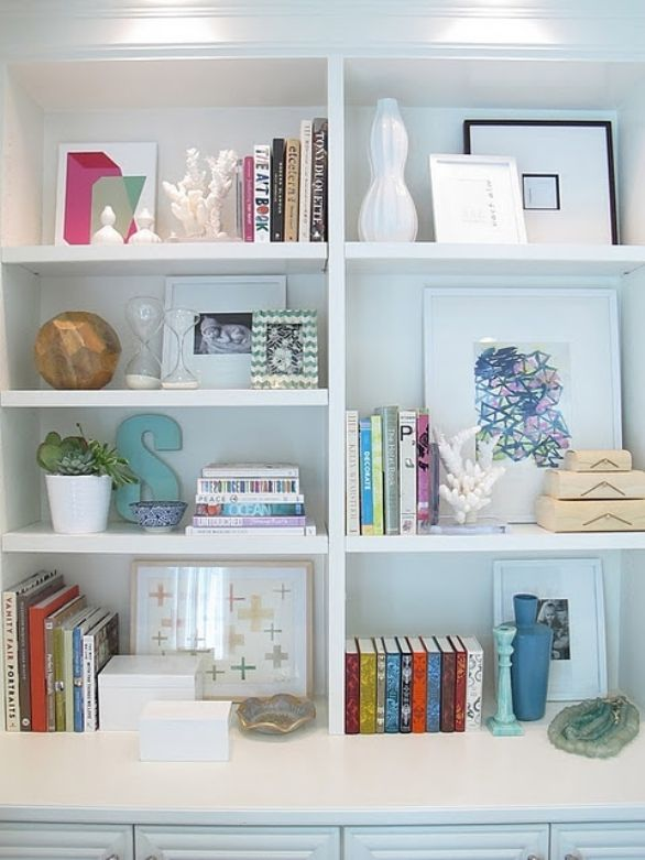 Book case styling. The monogram, the horizontal books, the succulent, the pops of blue.