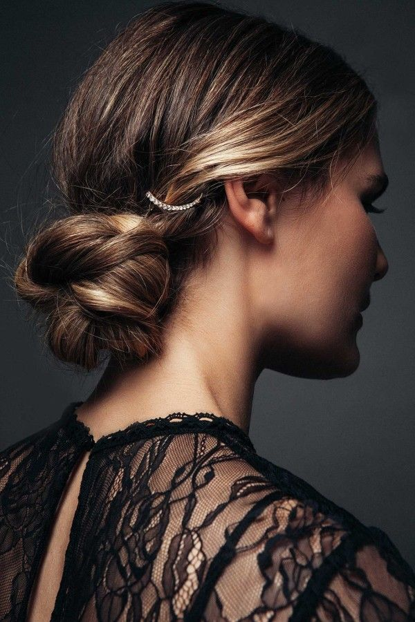 Ladylike Bun - On blow-dried hair, use a 1-inch wand to curl strandsin alternating directions. Spritz with a texturizing spray to create loose, tousled waves. Leaving out a 2-inch section on either side of your center part, pull hair into a low ponytail and secure with an elastic. Braid the ponytail and pull sections apart to thicken the plaits. Wrap the braid into a loose bun and pin. Pull front sections back, twist and pin. Finish with a crystal embellishment.