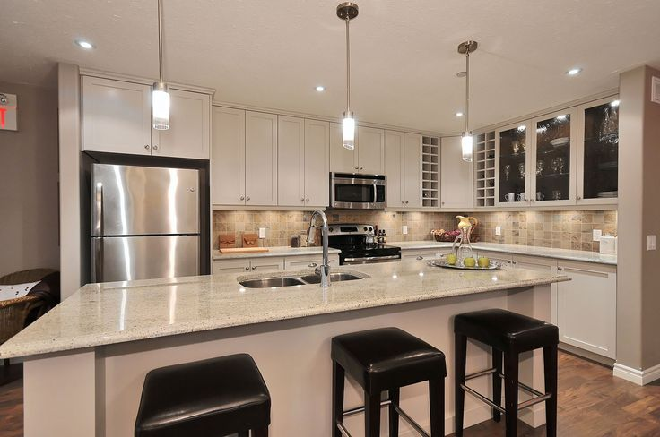 The Trent - Kitchen.  Benjamin Moore painted cabinets in Collingwood, kashmir white granite, stainless appliances, custom glass cabinets with swedish walnut interior & lights...  www.qualityhomes.ca