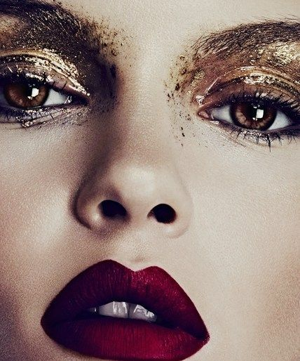 Glossy smudged with gold pigment artistic eye makeup + deep red lips.