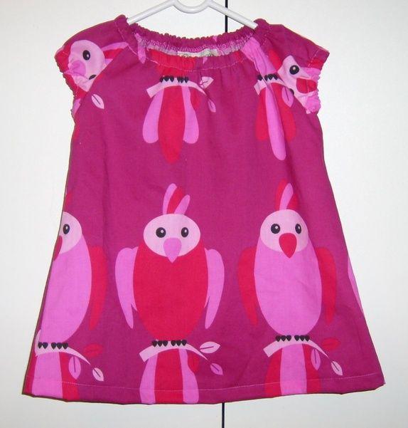 Kjole med papegøyer på str 92  Kjolen vokser med barnet og kan brukes som tunika senere.    Kjolen er laga av 52% polyester og 48% bomull   Kan vaskes på 40 grader