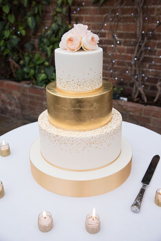 elegant gold and white wedding cake with floral topper / http://www.deerpearlflowers.com/amazing-wedding-cake-ideas/5/