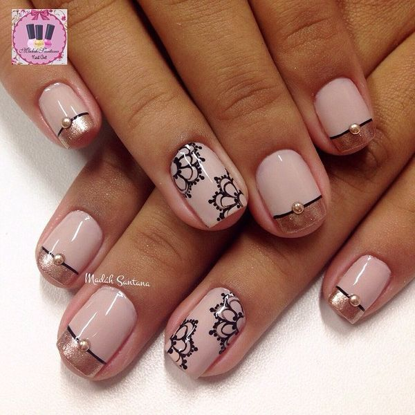 Pink and gold French tips. Elegant looking gold French tips on top of a pink base. Thin details of lace designs in black polish are also added on top with pink beads.