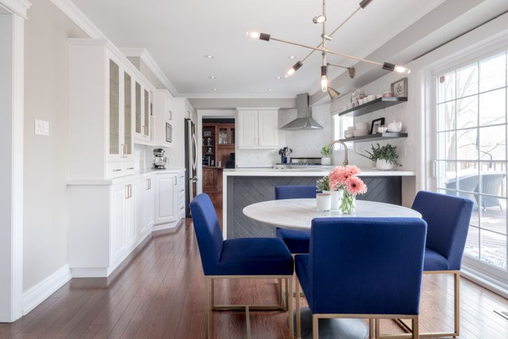 Open concept white kitchen with eat in area.  Blue chairs really pop against this neutral modern kitchen.