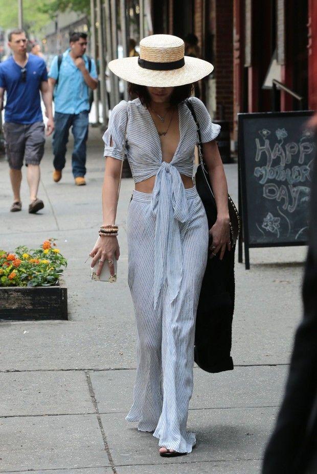 Vanessa Hudgens pelas ruas de Nova York , com conjunto listrado de top cropped e calça flare e chapéu de palha .