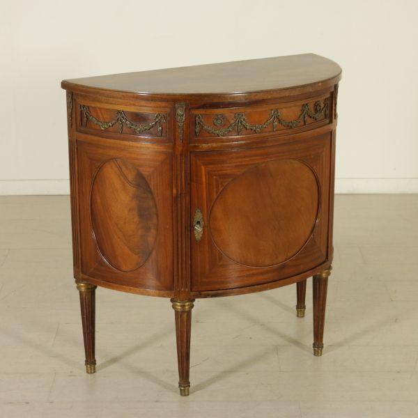 Credenza demilune presenta un'anta e un cassetto. Riserve ovali in piuma, fascia con bronzi.