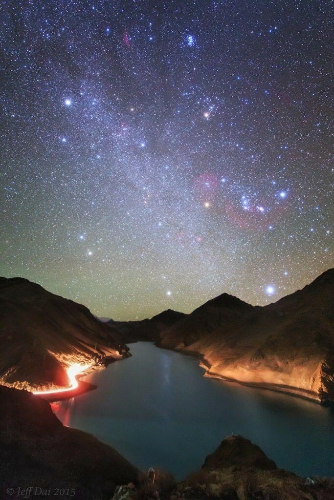 La Via Làctia, la constel·lació d'Orió i Sírius des del Tibet. Fotografia presa des de la reserva de Manla al Tibet. Es pot apreciar a Sírius, l'estrella més brillant del cel nocturn (el punt de llum més brillant abaix, al costat dret). A dalt de Sírius es troba la constel·lació d'Orió, mentre que la constel·lació de Taure és visible a dalt de la constel·lació d'Orió. Seguint al costat dret, a prop de la vora superior, s'ubiquen les Plèiades. Capella (de la constel·lació d'Auriga) és…
