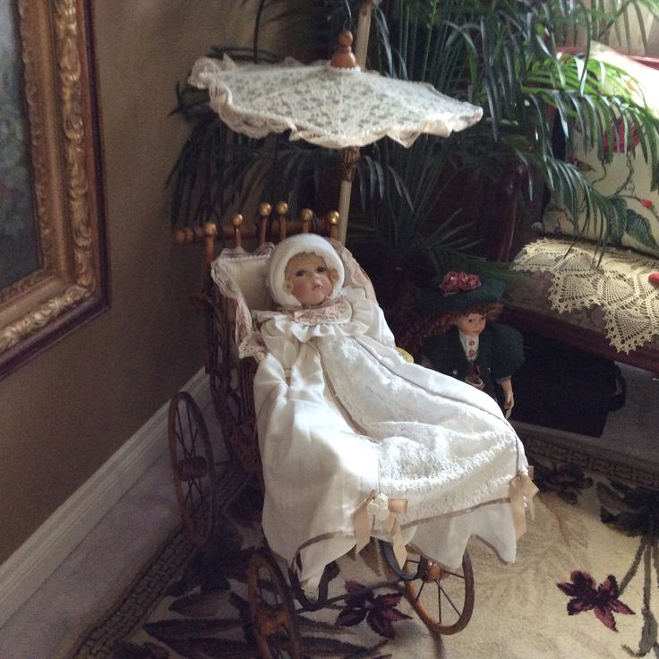 A COLLECTABLE BABY DOLL IN A VINTAGE PRAM