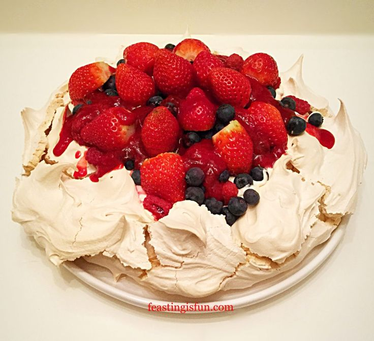 Raspberry Coulis Drizzled Mixed Berry Pavlova crunchy outer meringue shell hides a soft marshmallow centre. Thick cream topped with jewel coloured fresh fruits and drizzled with a tart raspberry coulis to balance the flavours. Beautifully easy to make this elegant dessert.