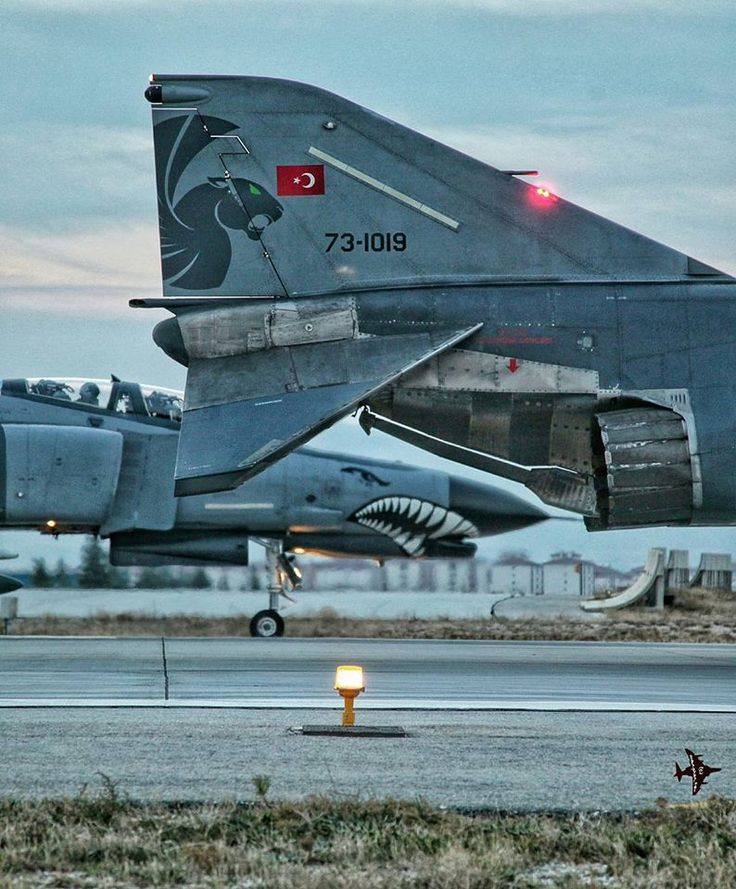 Two neatly-painted TuAF F-4E 2020 Terminators awaiting takeoff clearance at dusk.