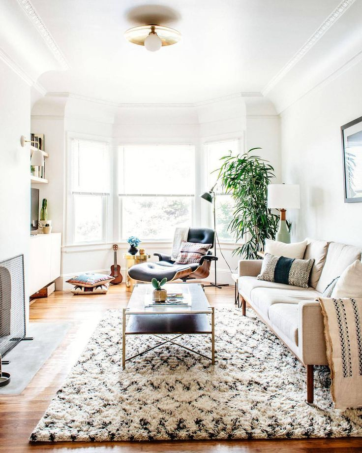Modern global chic style in a living room design featuring an Eames style lounge chair and ottoman, mid-century modern ceramic table lamp, contemporary beige upholstered sofa, global patterned pillows and throw, and a moroccan area rug - Neutral Home Decor & Decorating Ideas