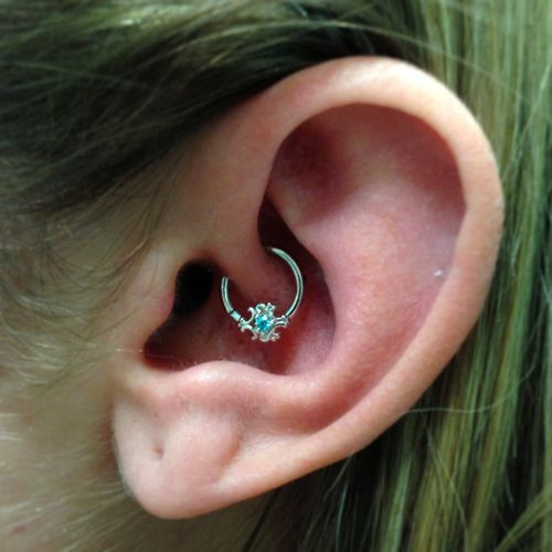 Cute little healed daith piercing with a white gold ring and Paloma swirl accent.