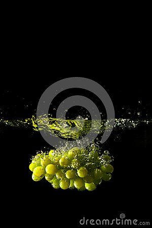 Grapes splash in water with droplets
